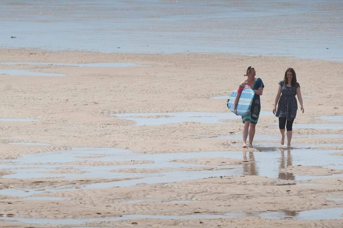 Two people walk on a beach at low tide carrying a surfboard