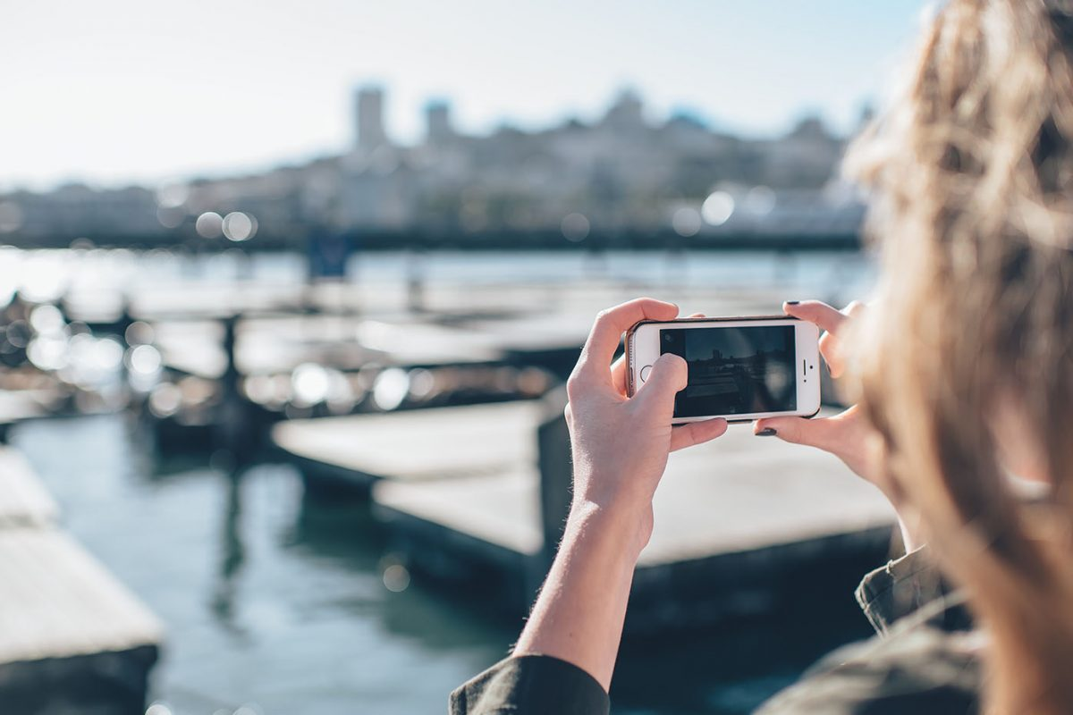 A woman takes a phone of a harbour on her iphone