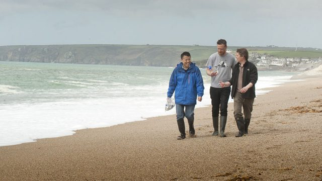 3 male researchers in discussion as they walk along a cloudy beach
