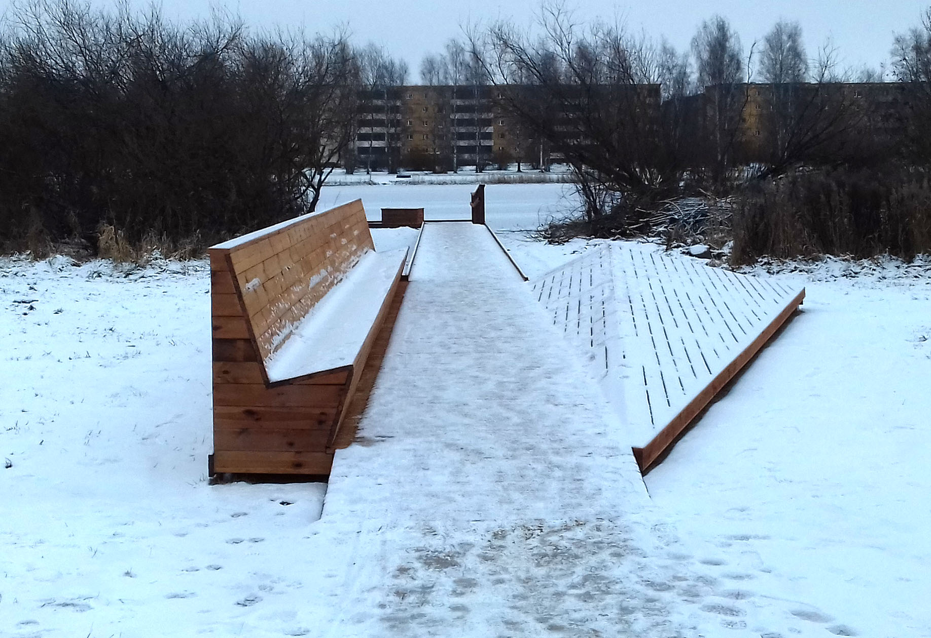 A bench and walk way lead to a snowy Anne Kanal