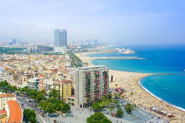 A view of Barcelona coastline with buildings meeting a blue ocean