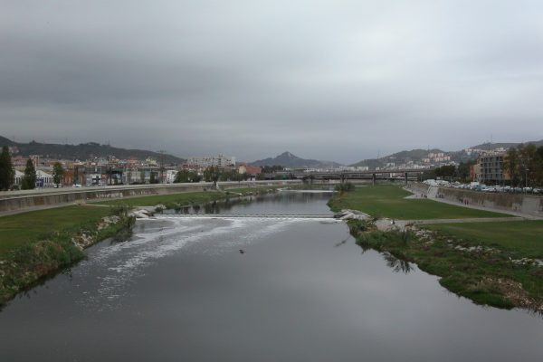A view of the Besos River (quite wide) with mountains in the background