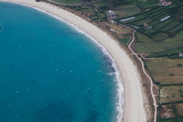 An aerial view of a white sand beach on the Isles of Scilly