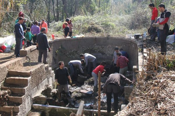 Volunteers work on Can Moritz fountain, moving soil, plants and rocks from a large semi-circular structure