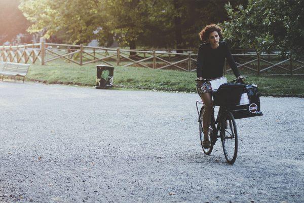 A woman cycles through an urban park at sunset