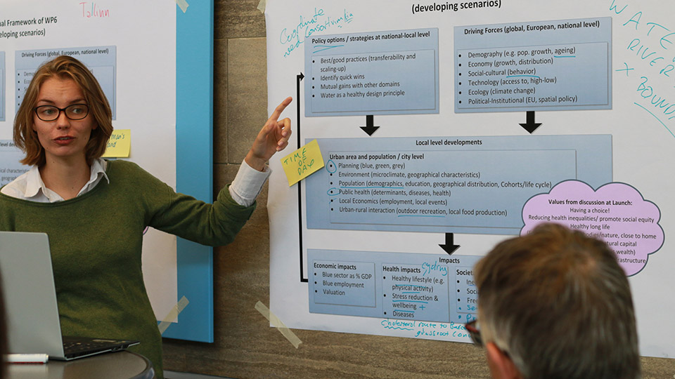A researcher talks through diagrams on a poster