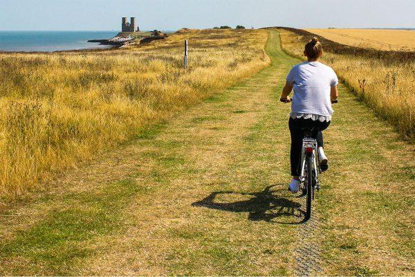 A woman cycles along a grassy coast path