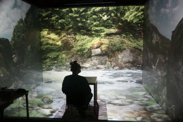 A person sits in a virtual reality 'cube' that projects images on every surface