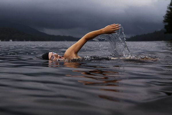 a woman takes a breath mid stroke whilst swimming in a lake on a cloudy day