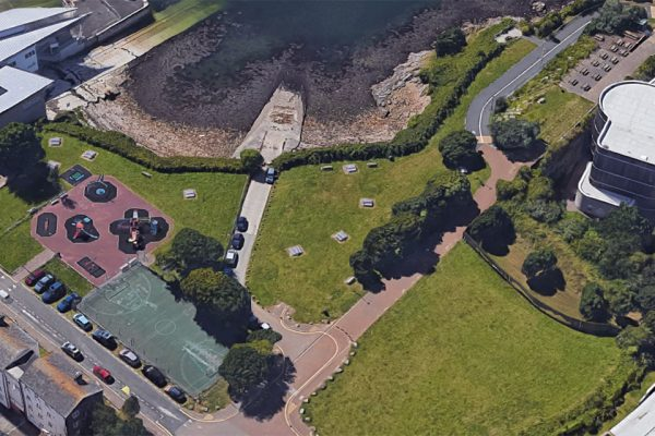 An aerial view of the Plymouth beach location, showing green spaces leading to a concrete slip way descending into rocky water