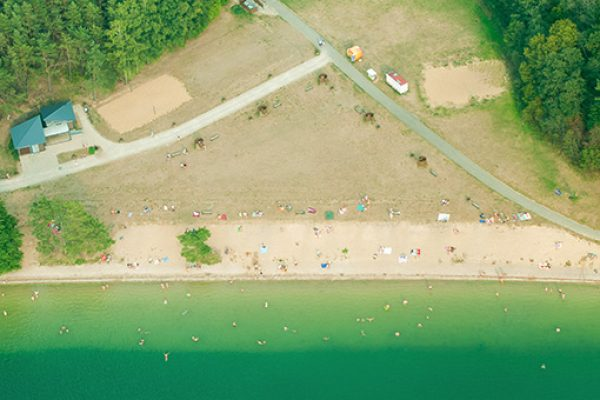 An aerial view of people using a green lake with coastal paths criss-crossing and trees close to the water