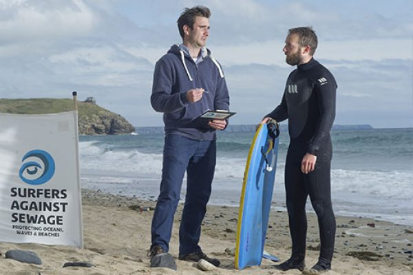 A researcher talks to a surfer on the beach