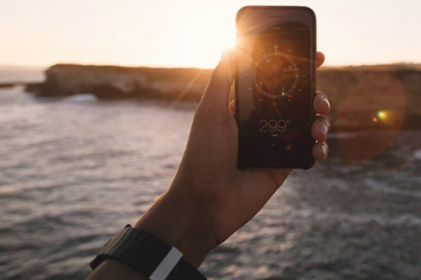 BEAT tool - A person holds a phone up to read the compass app with the sea in the background