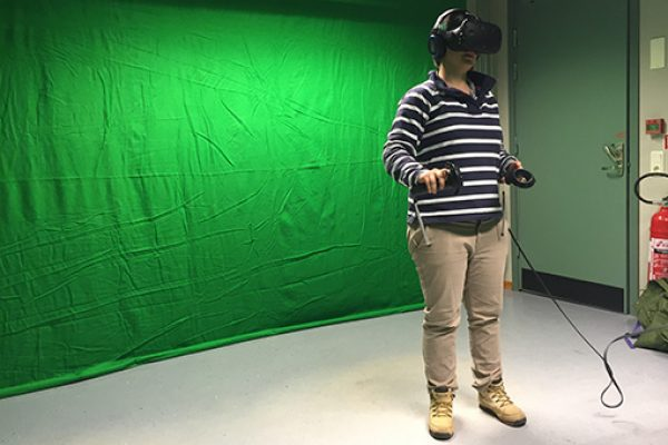 A person stands in front of a green screen with a virtual reality headset on for the BlueHealth project
