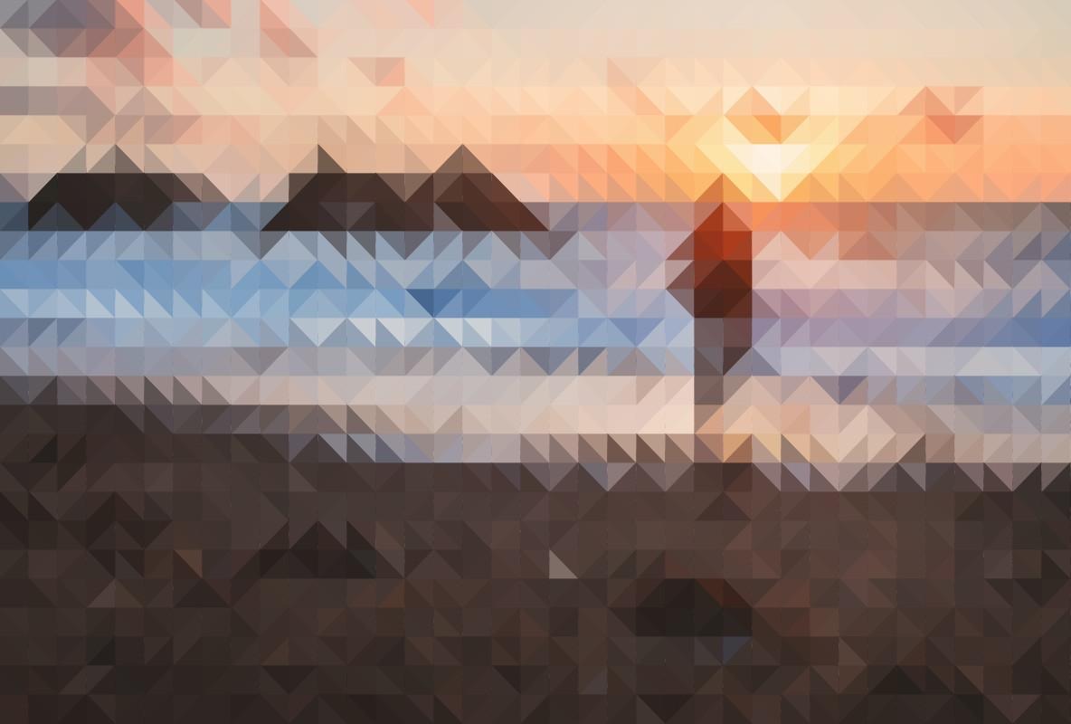 A man walks along the seashore as the sun sets on the horizon