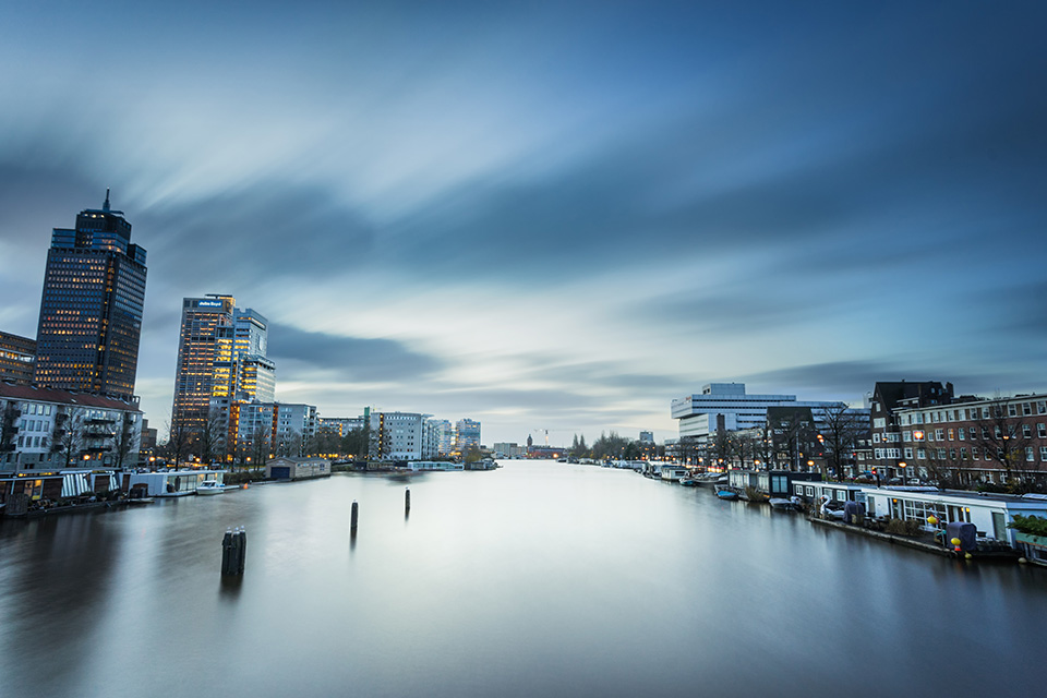 A grey sky reflects in an urban river with buildings either side bluehealth