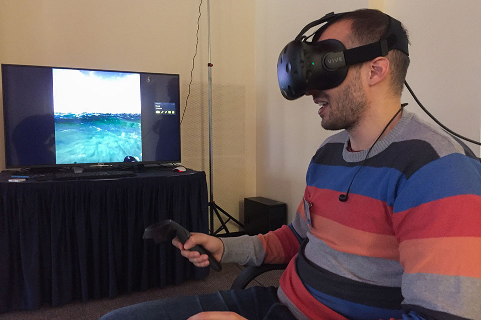 A man sits in a chair with a VR headset on - a screen behind shows a virtual beach