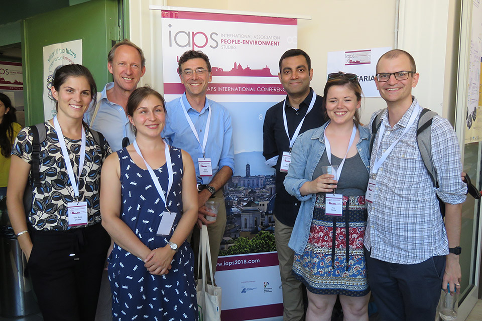 BlueHealth researchers smile in front of an IAPS banner