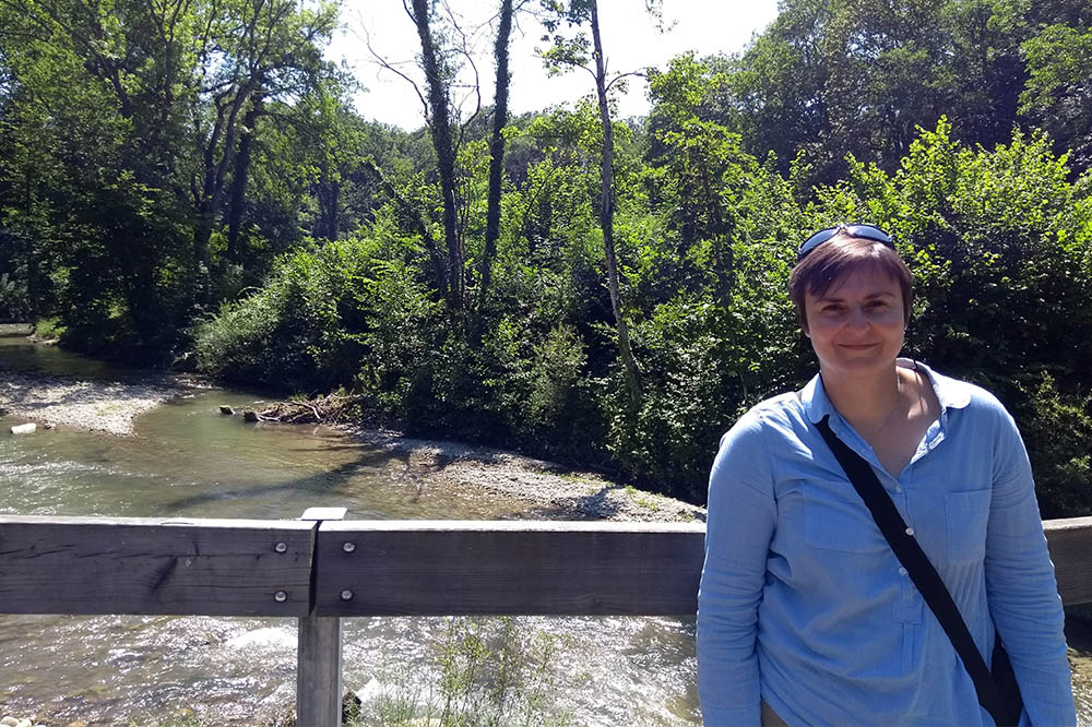 Sandrine standing on a bridge in front of a shallow rocky river