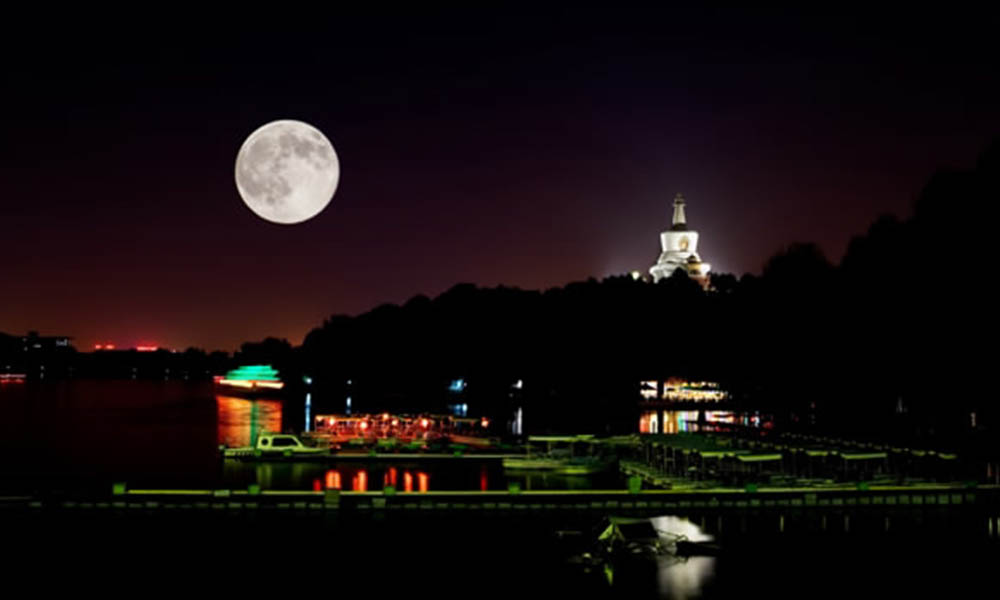 A full moon rises over the lake in Beihai park