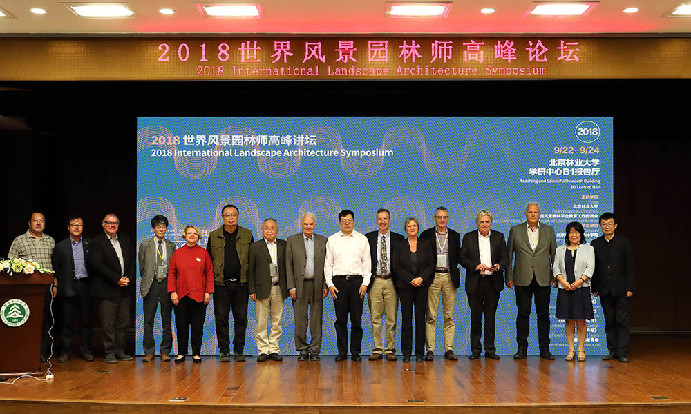 Delegates of the symposium line up for a photo on stage