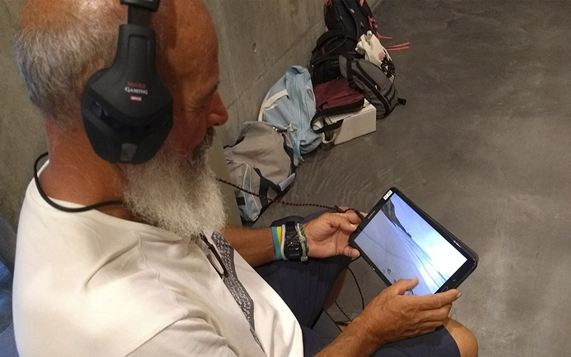 A man looks at a video of a blue space on a digital tablet