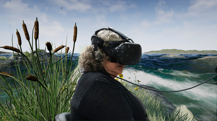 A woman sits in a VR headset with a digital environment behind her
