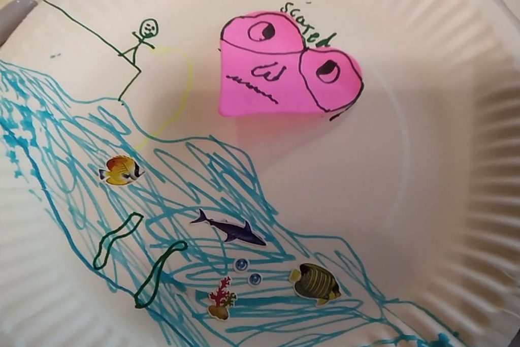 One child draws their concerns about the sea