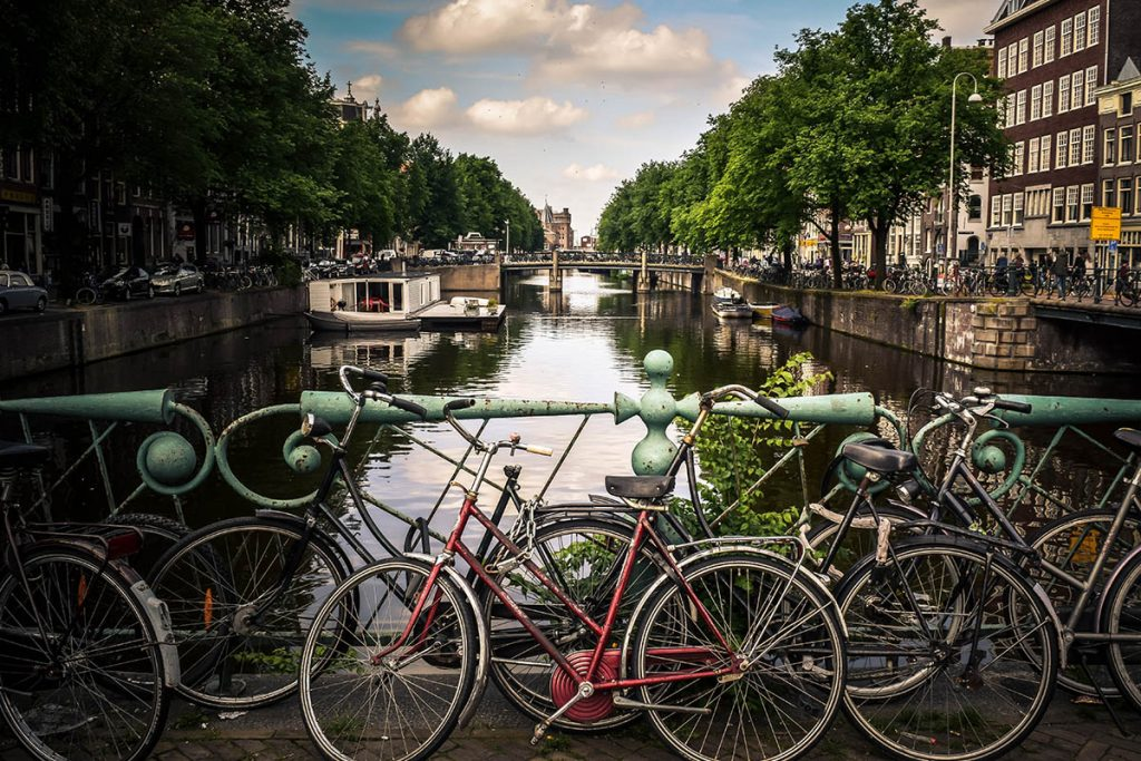 Cyclists park their bikes along the canals in Amsterdam