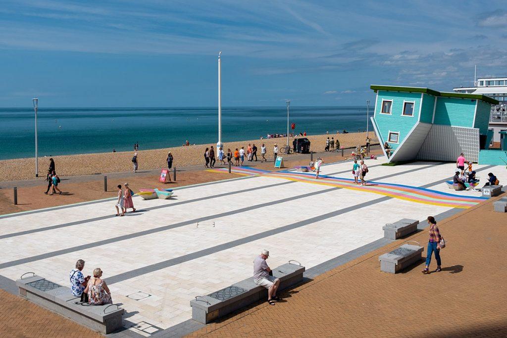 People walk along the beach promenade in the city of Brighton