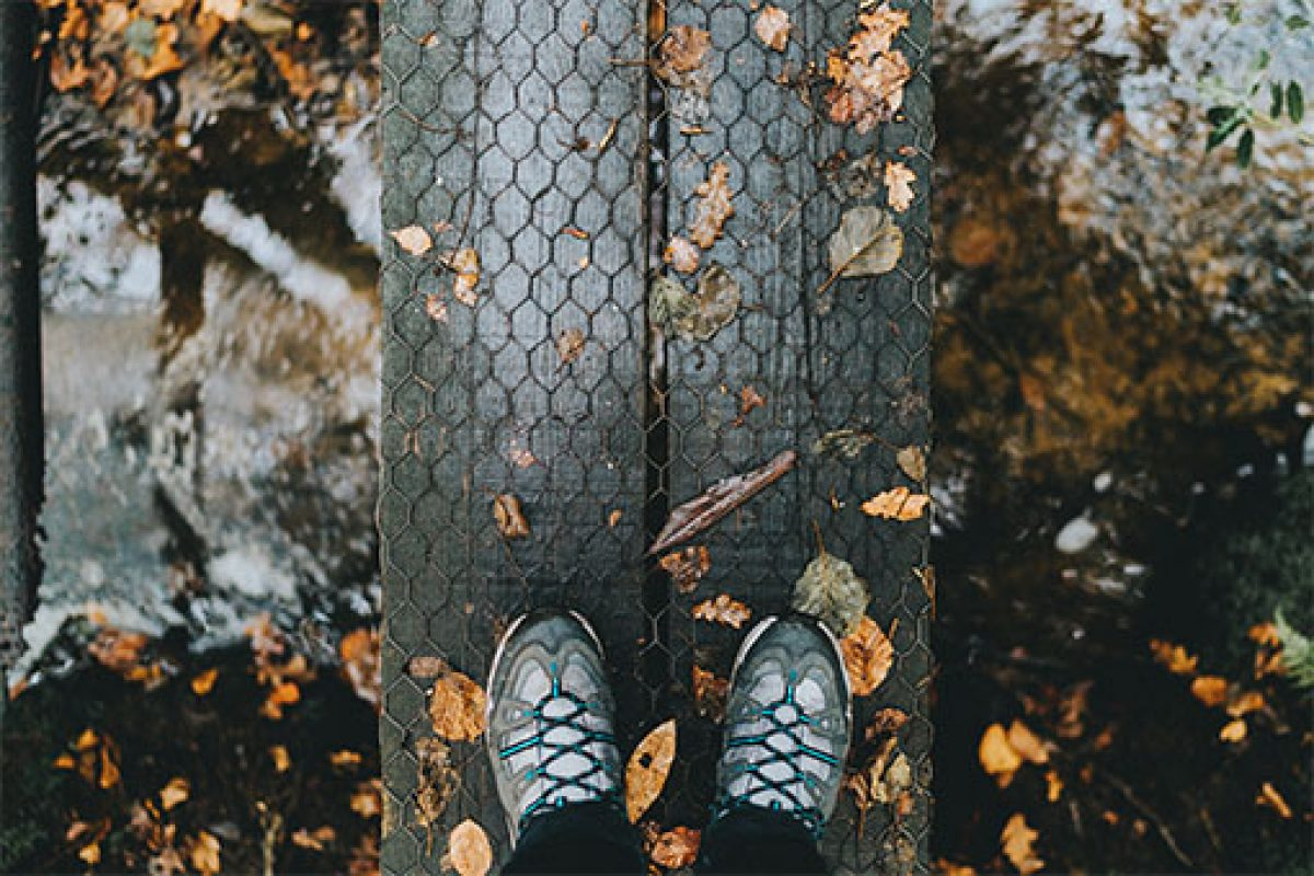 Autumn photo of someone's walking boots as they step on a bridge over a stream